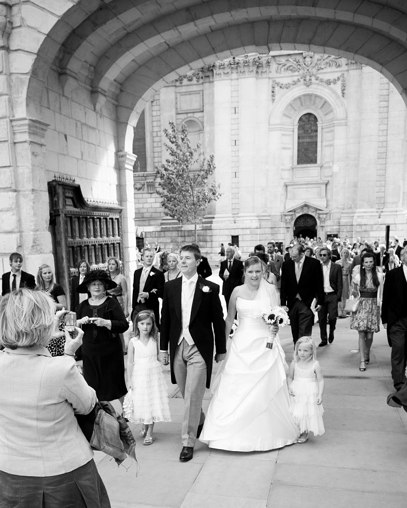 Bride and groom enter Paternoster Square. St Paul's Cathedral wedding photographer Wild Weddings