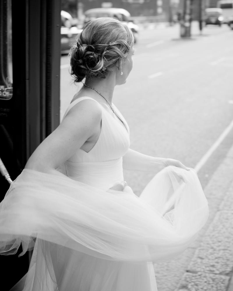 Bride gets off London bus. Knightsbridge wedding photographer Wild Weddings