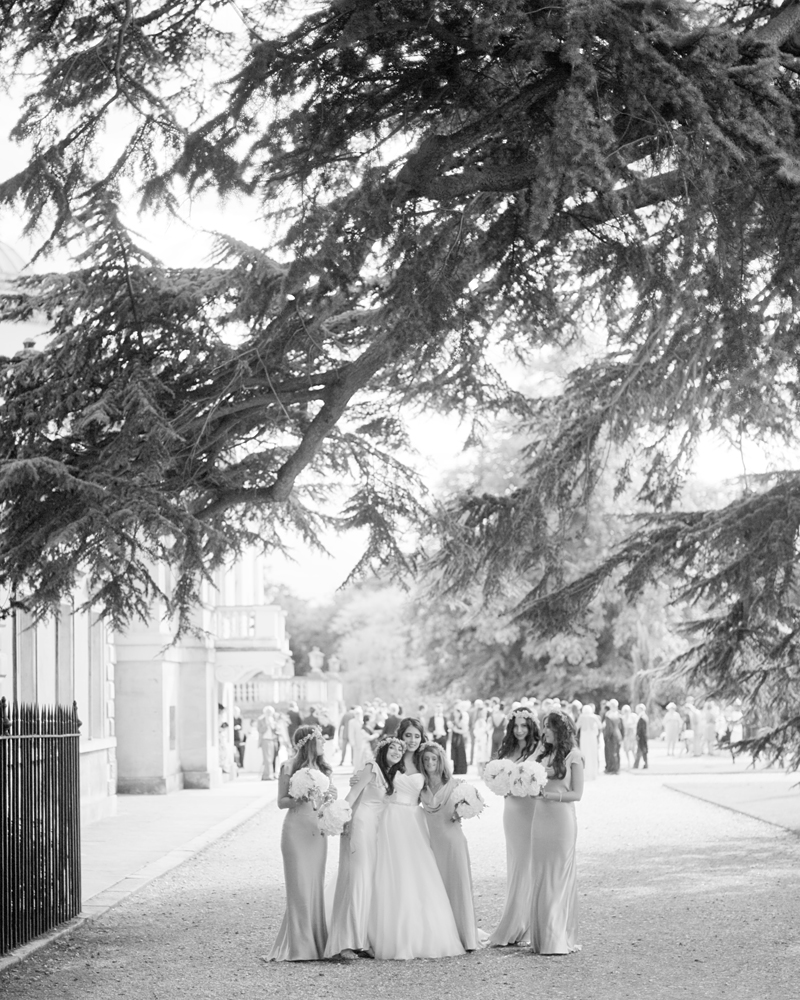 Bride and bridesmaids walk the grounds. Chiswick House wedding photographer Wild Weddings