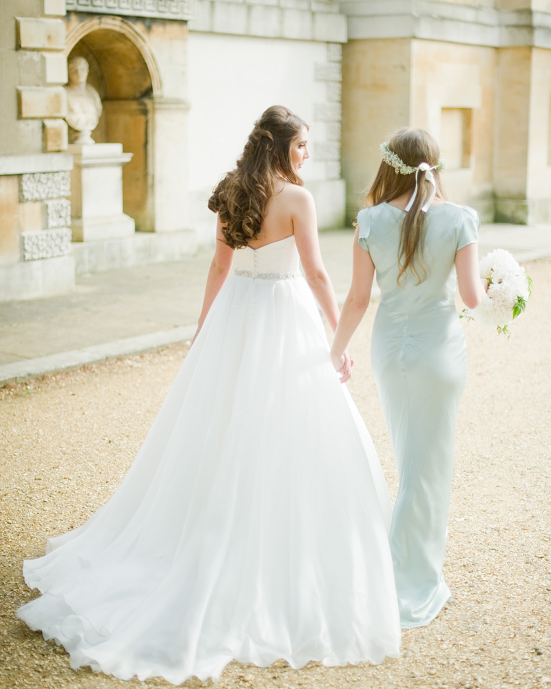 Bride and bridesmaid walk the grounds. Chiswick House wedding photographer Wild Weddings